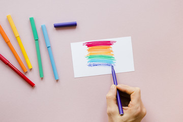 Person drawing rainbow with felt pen