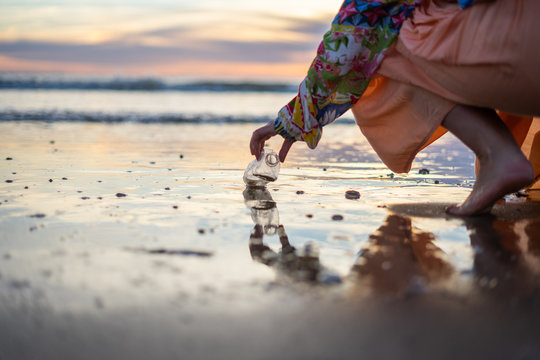 A woman cleaning a beach full of plastic bottles and rubbish in the sea