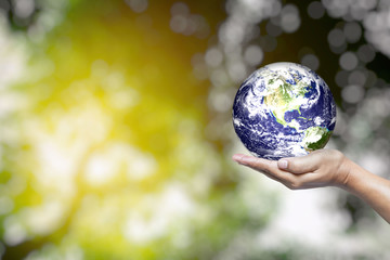 World in Hand and Blurred Beautiful Bokeh in the Garden Background with Space for Text, Suitable for Business and Environment Concept. Elements of this Image Furnished by Nasa.