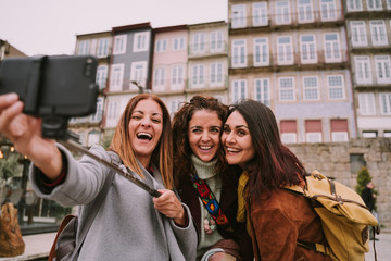 Three young and beautiful women friends are taking a picture while touring the city of Porto. The three women friends are enjoying the place together and laughing while being photographed.
