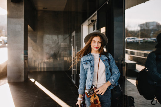Cute pretty girl in hat with lovely face expression posing outside while wind playing with her hair before shopping. Charming female photographer in denim outfit standing on the street holding camera