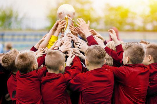 Children's soccer team raising golden football trophy
