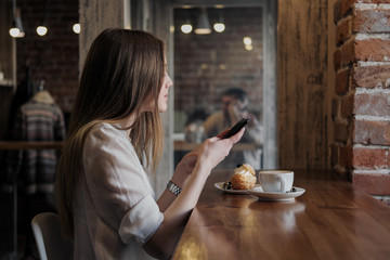 A young beautiful brunette girl in a loft-style cafe sits at a table by the window, drinks coffee and uses a smartphone, calls, takes pictures.