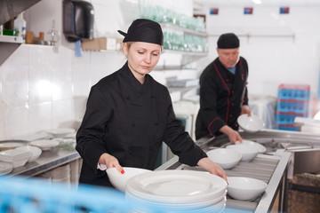 Woman arranging clean dishware