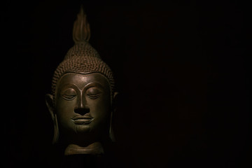 Head Buddha statue with aura used as amulets of Buddhism religion on black dark light and shadow background. soft focus