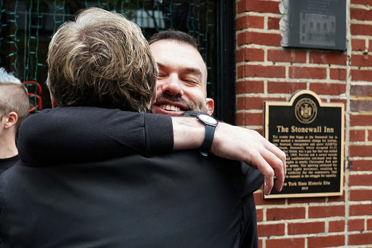 Members of The San Francisco Gay Men's Chorus hug after they sang on the street in front of the historic gay bar the Stonewall Inn in the Manhattan borough of New York