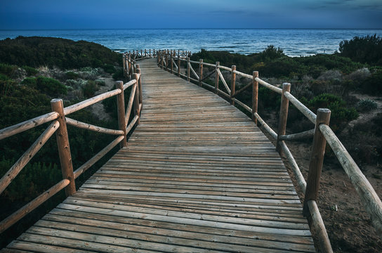 Lumber pathway leading to rippling sea on tranquil evening in countryside in Cabopino, Artola dunes. Marbella, Spain