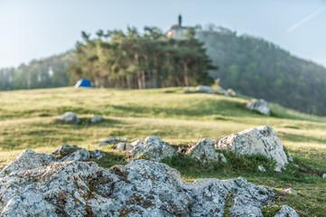 Felsformation mit Wiese vor Baumgruppe mit Campingzelt und Burg Teck