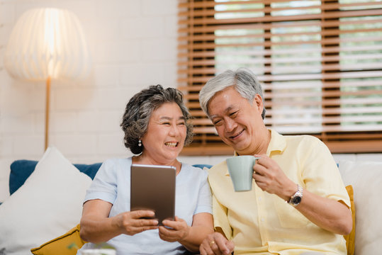 Asian elderly couple using tablet and drinking coffee in living room at home, couple enjoy love moment while lying on sofa when relaxed at home. Enjoying time lifestyle senior family at home concept.