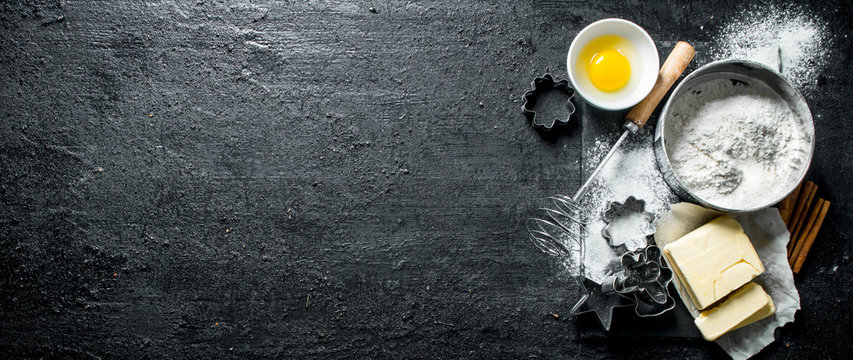 Baking background. Flour with egg, butter and various forms for baking.