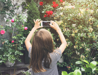 young girl take a mobile picture with her smart phone of beautiful flowers in garden