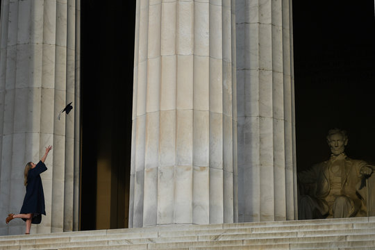 A woman throws her graduation mortar board cap in the air as she poses for her photographer in front of the Lincoln Memorial in Washington