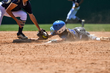 Young high school softball players in action, making amazing plays, during a game