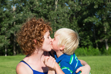 A Mother Holds And Kisses Her Young Son; Stony Plain, Alberta, Canada