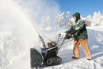 A Man Happily Using His Snowblower In Front Of His House; Alaska, United States Of America