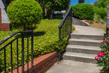 Concrete stairs and curving walkway bordered by brick retaining wall and groundcover, horizontal aspect