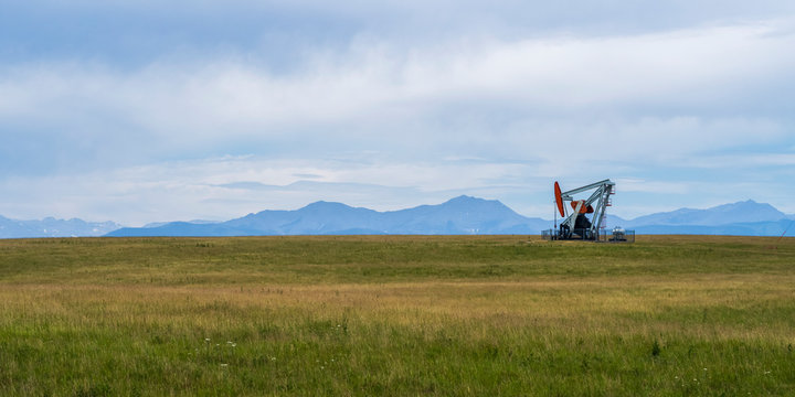 A pump jack at an oil well in a grass field with the Canadian Rocky mountains in the distance; Alberta, Canada