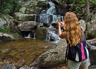 A woman takes a cell phone picture of Laurel Falls on a summer day in Great Smokey Mountains National Park; Sevierville, Tennessee, United States of America