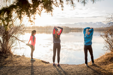 Three young women stretching on a trail at the water's edge; Anchorage, Alaska, United States of America