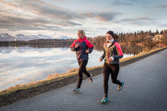 Two young women running on a trail at the water's edge with mountains in the distance; Anchorage, Alaska, United States of America
