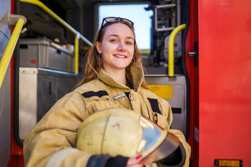 Image of smiling woman firefighter with glasses on head with helmet in hands standing next to fire truck
