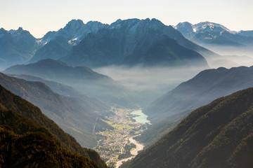 Sunrise with illuminated fog laying through the mountain range and over a valley; Sesto, Bolzano,Italy