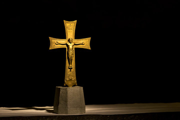 Gold crucifix dramatically illuminated with black background; Florence, Tuscany, Italy