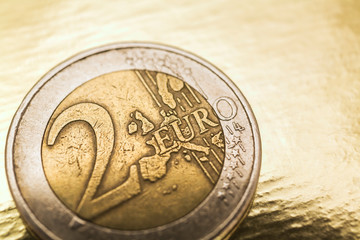 Two Euros coin on gold background