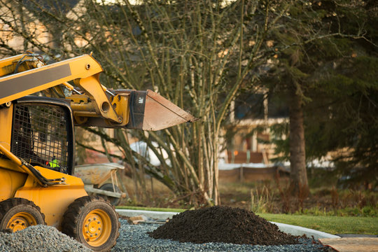 Small front end loader moving and placing gravel in a park area for new home construction; Langley, British Columbia, Canada