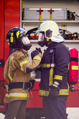 Picture of firefighters women and men in helmet and mask looking at each other and doing handshake near fire truck