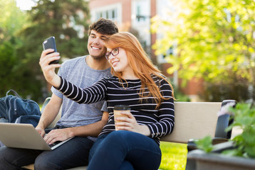 A young man and young woman sit together on a bench on the university campus taking a self-portrait on a smart phone while drinking coffee; Edmonton, Alberta, Canada