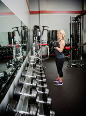 Fitness club owner teaching how to lift free weights while watching herself in the mirror at her fitness facility; Spruce Grove, Alberta, Canada