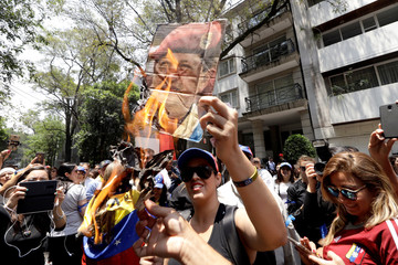 Supporters of Venezuelan opposition leader Juan Guaido burn a picture of late Venezuela's President Hugo Chavez during a protest outside the Venezuelan embassy in Mexico City
