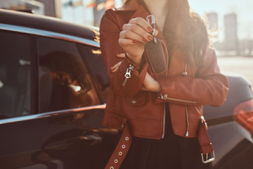 Women in red leather jacket just sold her car, which is behide her. She holds key. There are sunny day.
