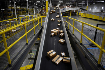 Boxes ready to be loaded onto a delivery truck move along a conveyor belt at the Amazon fulfillment center in Baltimore