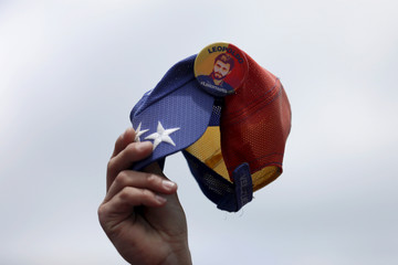 A person holds up a cap with an image of Leopoldo Lopez during a protest in Bogota