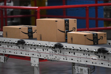 Packed and labeled boxes ready for delivery move along a conveyor belt at the Amazon fulfillment center in Baltimore