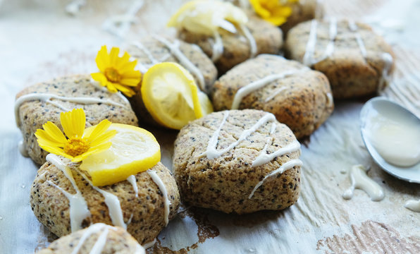 Lemon poppy seed bread squares with icing and lemons as garnish on food.