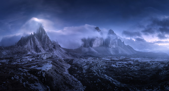 Mountains in fog at beautiful night. Summer landscape with mountain valley, stones, grass, blue sky with low clouds, stars and moon. High rocks at dusk. Tre Cime park in Dolomites, Italy. Italian alps