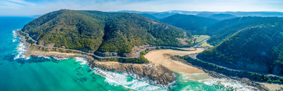 Wide aerial panorama of Great Ocean Road bending and winding along scenic coastline