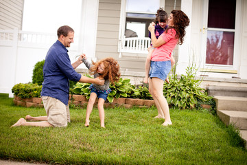 Happy Family Playing in Yard in Front of Their Home Wall mural