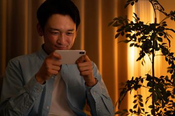 スマートフォンでコンテンツを見る男