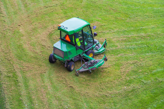 A riding commercial landscaper of a community or city services on the big lawn mower cutting the grass