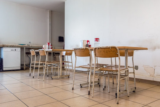 Empty dining hall with old chairs and water-bottles on tablesin a factory
