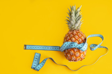 Blue measuring tape around fresh pineapple with copy space  as exercise, health and diet concept.