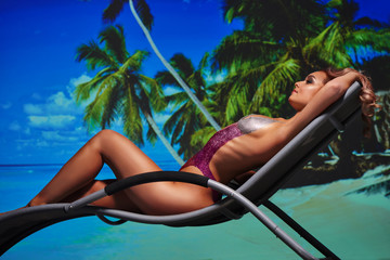 girl in a swimsuit suit painted on a beach lounger body paint
