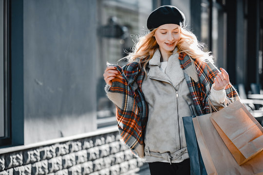 Elegant lady in a winter city. Stylish girl walking with shopping bags. Blonde in a cute beret