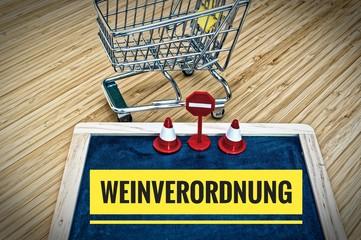 Tafel mit Einkaufskorb und Aufschrift in deutsch Weinverordnung in englisch wine ordinance