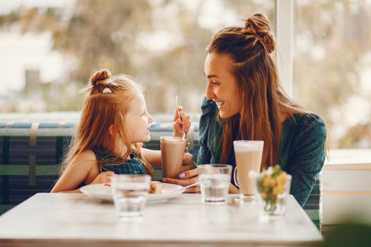 young and stylish mother with long hair and a green dress sitting with her little cute daughter in the summer cafe and she feeds her daughter with a dessert