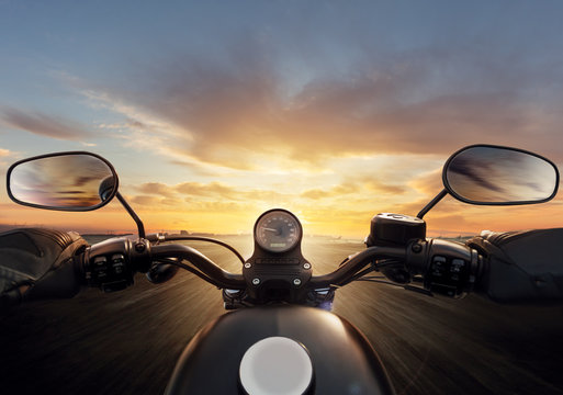 POV of motorcycle driver with handlebars.